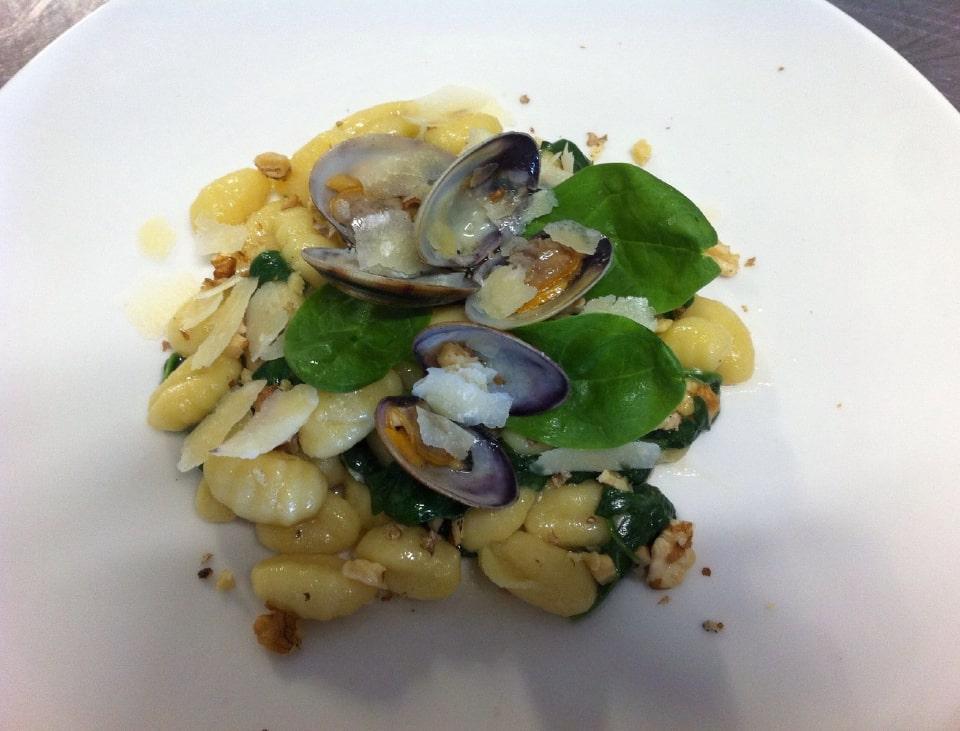 Gnocchetti con spinacino, noci, vongole e scaglie di grana